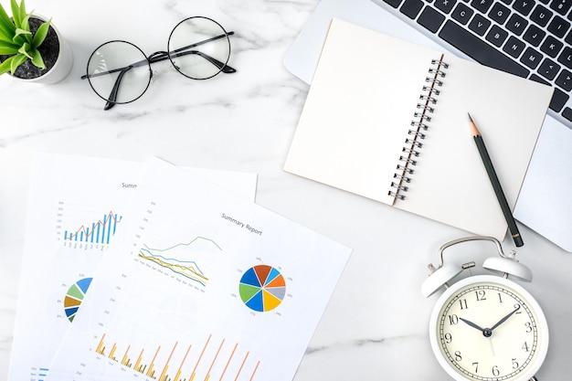 Widok z góry koncepcji pracy biurka biurowego z pustym notatnikiem, raportem, budzikiem na marmurowym białym tle, pojęciem zarządzania czasem i planowania harmonogramu.