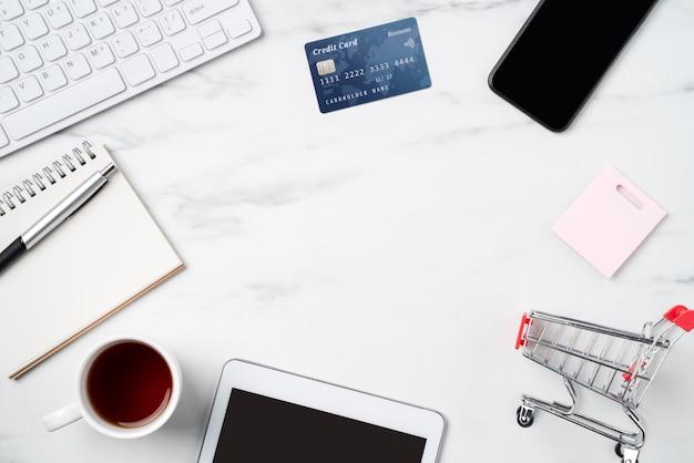 Widok z góry koncepcji zakupów online z kartą kredytową i elektroniką na białym tle na marmurowym stole w biurze.