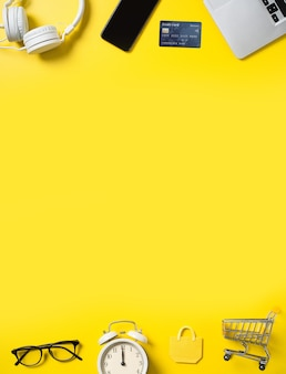 Widok z góry koncepcji zakupów online z kartą kredytową, inteligentny telefon i komputer na białym tle na żółtym tle tabeli biurowej.
