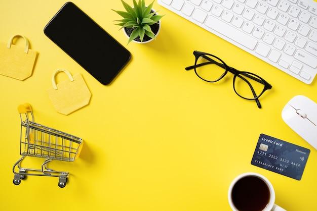 Widok z góry koncepcji zakupów online z kartą kredytową, smartfonem i komputerem na białym tle na biurowym tle żółty stół.