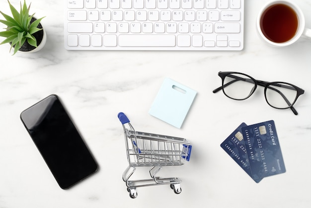 Widok z góry koncepcji zakupów online z kartą kredytową, smartfonem i komputerem na białym tle na tle marmurowego stołu w biurze.
