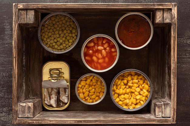 Widok z góry konserwowane puszki po żywności w drewnianej skrzyni