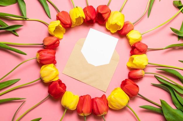 Widok z góry koperty i ramki czerwonych tulipanów na różowym tle.