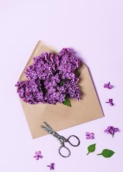 Widok z góry koperty rzemieślniczej z fioletową gałązką bzu i rustykalnymi nożyczkami