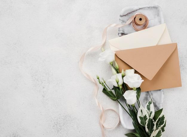 Widok z góry koperty zaproszenia ślubne z kwiatami
