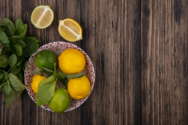 Widok z góry kopia przestrzeń cytryny z limonki na talerzu z klinami i miętą na drewnianym tle