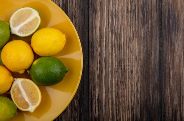 Widok z góry kopia przestrzeń cytryny z limonki na żółtym talerzu na drewnianym tle