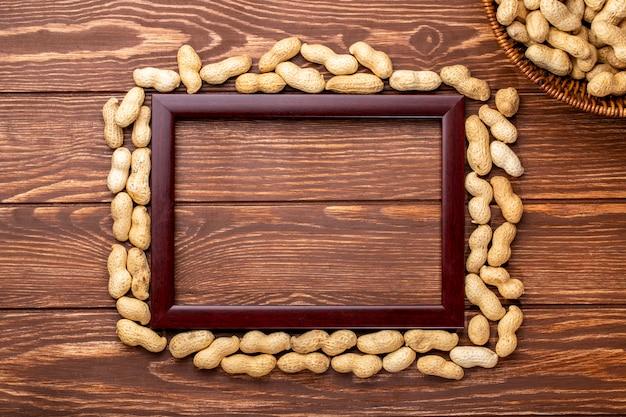 Widok z góry kopia przestrzeń drewniana rama wokół krawędzi orzeszki ziemne w skorupkach na drewnianym stole