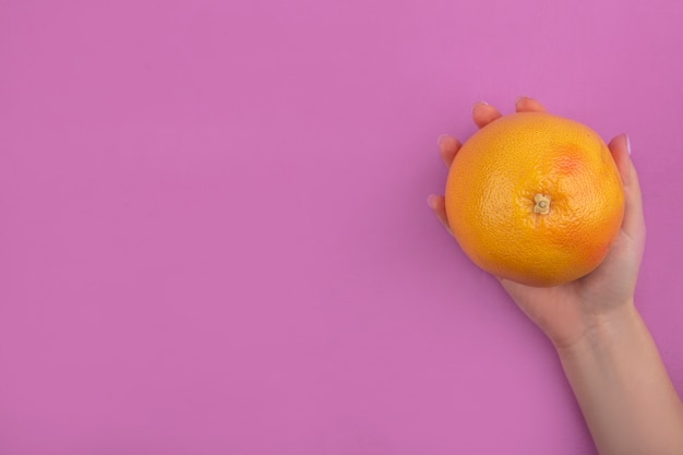 Widok z góry kopia przestrzeń kobieta trzyma w ręku grejpfruta na różowym tle