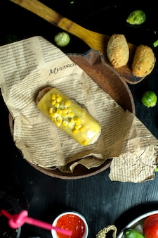 Widok z góry kotlety z kurczaka z kukurydzą i serem śmietankowym na gazecie na patelni