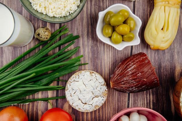 Widok z góry koziego sera z wędzonym serem zielona cebula i marynowane oliwki na rustykalnym drewnie