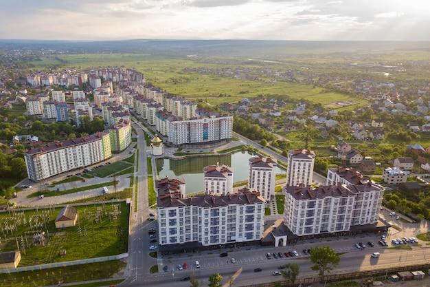 Widok z góry krajobrazu rozwijającego się miasta z wysokimi apartamentowcami i domami na przedmieściach.