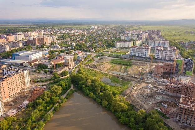 Widok z góry krajobrazu rozwijającego się miasta z wysokimi apartamentowcami i domami na przedmieściach