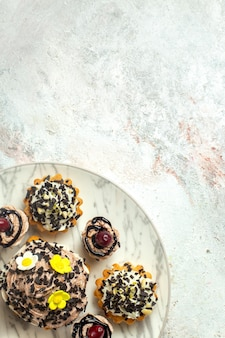 Widok z góry kremowe pyszne ciasta z czekoladowymi cipkami na jasnej białej powierzchni ciasto herbatniki ciastko herbata słodki krem