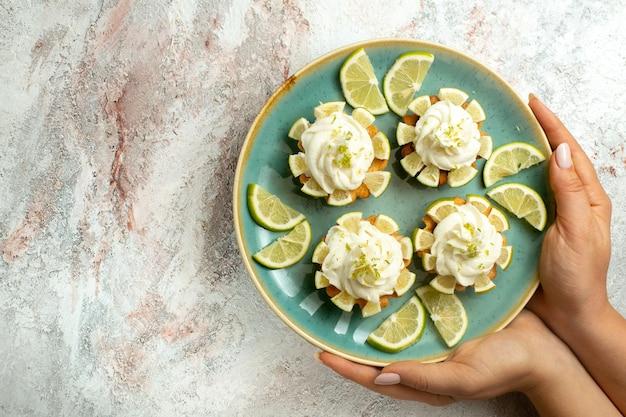 Widok z góry kremowe pyszne ciasta z plasterkami cytryny na białej powierzchni ciasto herbatniki ciastko krem herbata słodka