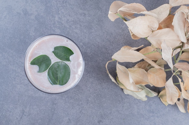 Widok z góry kremowego koktajlu mlecznego z liśćmi mięty na szarym tle.