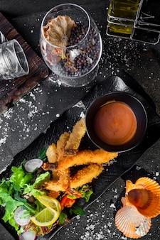 Widok z góry krewetki w cieście z sosem i sałatką ze świeżych warzyw i kieliszek do wina na tacy