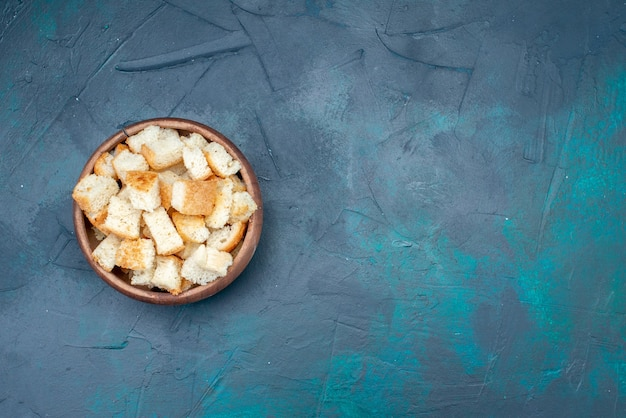 Widok z góry krojony chleb wewnątrz brązowej miski na ciemnoniebieskim zdjęciu kolorowej przekąski na biurku