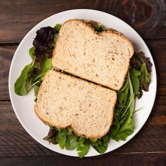 Widok z góry kromki chleba na liściach sałaty