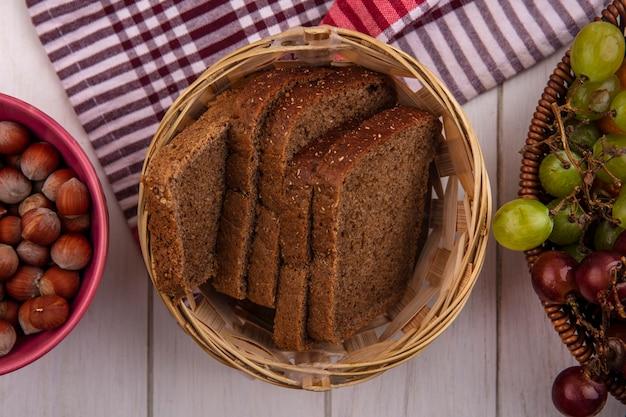Widok z góry kromki chleba żytniego w koszu na kratę szmatką z miską orzechów i koszem winogron na podłoże drewniane