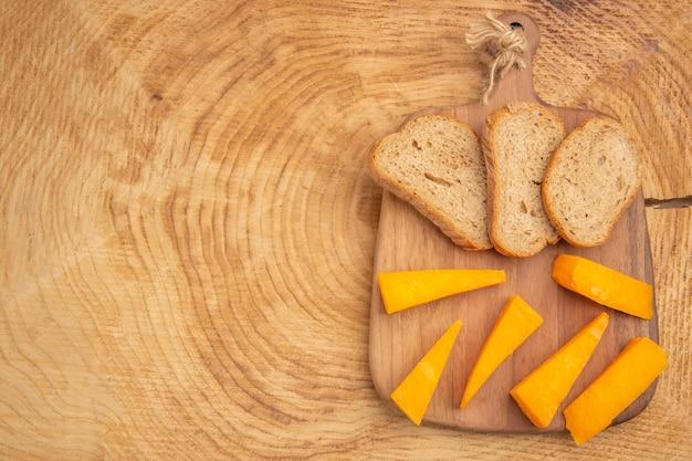 Widok z góry kromki sera kromki chleba na desce do krojenia na drewnianym stole z miejscem na kopię