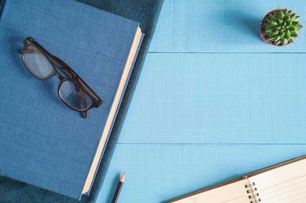 Widok z góry książki i notatki ołówek na niebieskim stole drewna
