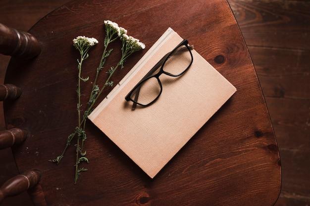 Widok z góry książki, kwiaty i okulary