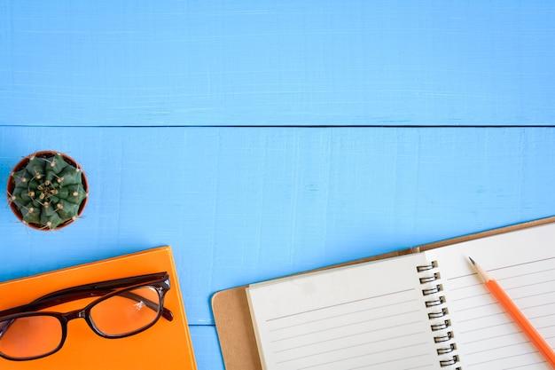 Widok z góry książki makieta i ołówek na niebieski stół z drewna