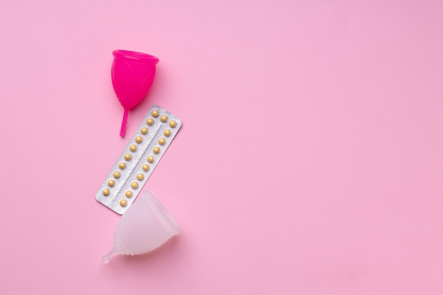 Widok z góry kubek menstruacyjny i doustne tabletki antykoncepcyjne