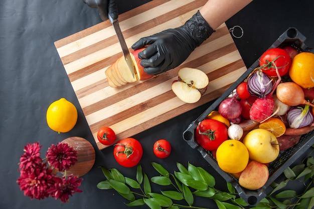 Widok z góry kucharz krojący jabłko na ciemnej powierzchni