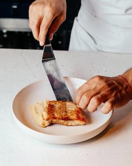 Widok z góry kucharz przygotowujący posiłek na białym talerzu iw kuchni posiłek obiadowy