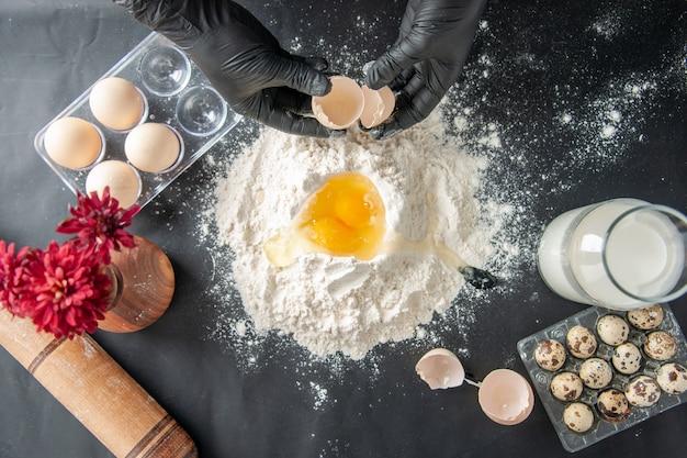 Widok z góry kucharz rozbijający jajka na mąkę na ciemnej powierzchni