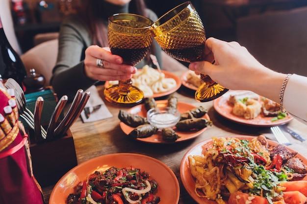 Widok z góry kuchni gruzińskiej na brązowym drewnianym stole. tradycyjne gruzińskie jedzenie - chinkali, kharcho, chahokhbili, phali, lobio i lokalne sosy - tkemali, satsebeli, adzhika. widok z góry. miejsce na tekst