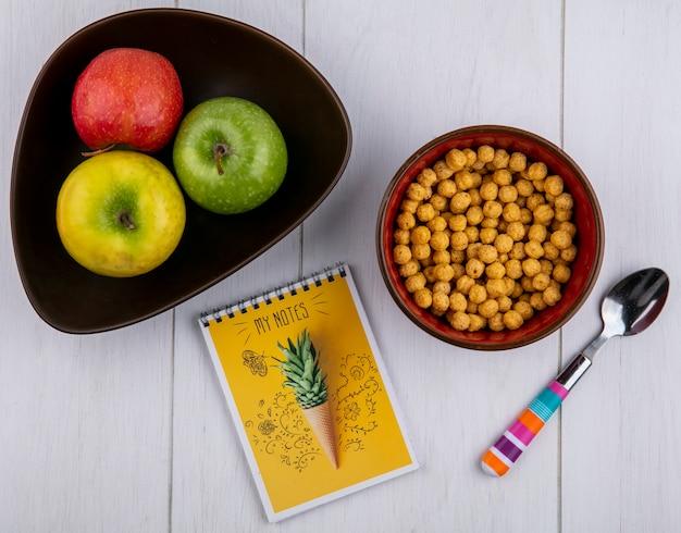 Widok z góry kulek kukurydzy w misce z kolorową łyżką kolorowe jabłka w misce z notatnikiem na białej powierzchni