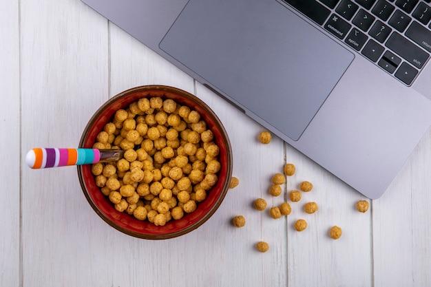 Widok z góry kulek kukurydzy w misce z laptopem na białej powierzchni