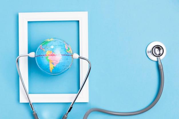 Widok z góry kuli ziemskiej w ramce z stetoskop