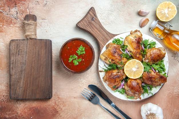 Widok z góry kurczaka kurczaka z ziołami cytrynowymi na desce widelec olejowy nóż deska do krojenia
