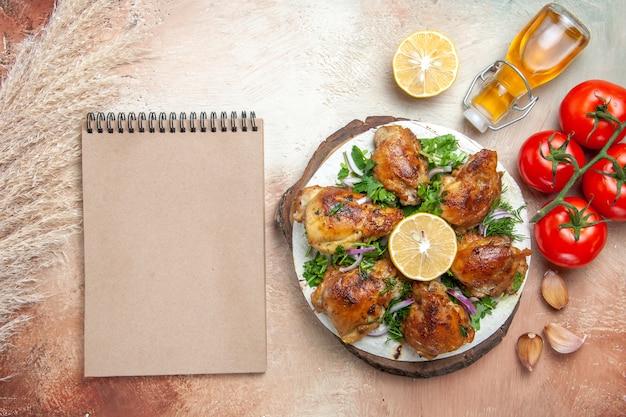 Widok z góry kurczaka, olej, pomidory, czosnek, cytryna, kurczak, z ziołami, śmietaną, notebook