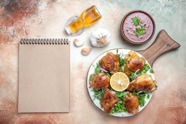 Widok z góry kurczaka z sosem kurczaka z ziołami na zeszycie z kremem czosnkowym i olejem lawaszowym