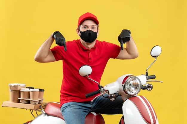 Widok z góry kuriera w czerwonej bluzce i rękawiczkach w masce medycznej, dostarczającego zamówienie, siedząc na skuterze skierowanym w dół