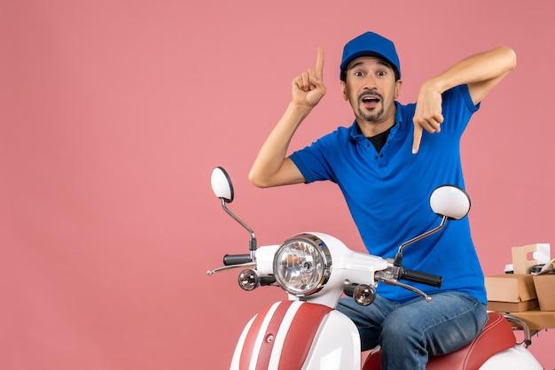 Widok z góry kuriera z kciukami do góry i kciukami w dół w kapeluszu siedzącym na skuterze dostarczającym zamówienia na pastelowym brzoskwiniowym tle