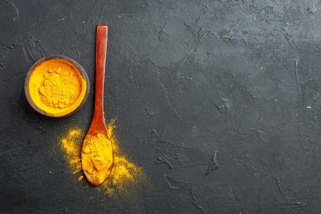 Widok z góry kurkuma miska kurkuma w drewnianej łyżce na ciemnym stole z wolną przestrzenią