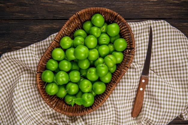 Widok z góry kwaśnych zielonych śliwek w wiklinowym koszu i nóż kuchenny na kraciastej tkaninie na ciemnym drewnianym stole