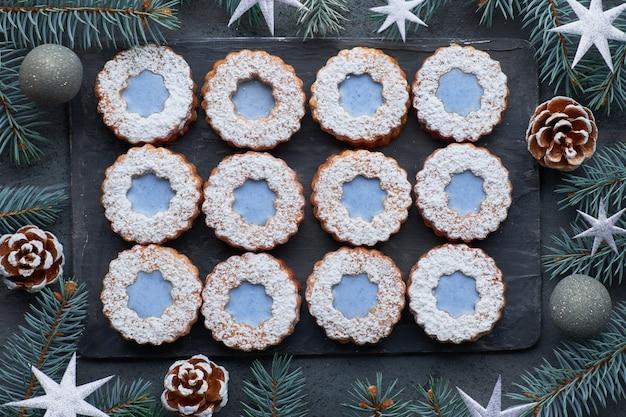 Widok z góry kwiatów ciasteczka linzer z niebieskimi szybami na ciemnej ścianie zima