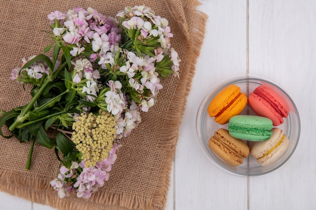 Widok z góry kwiatów na beżowej serwetce z kolorowymi makaronikami w słoiku na białej powierzchni