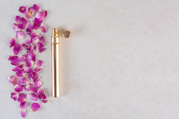 Widok z góry kwiatów z perfumami na szaro.