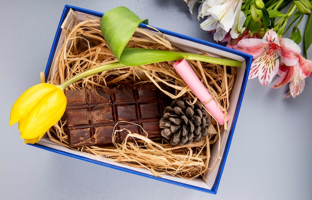 Widok z góry kwiatu tulipana w kolorze żółtym z ciemną tabliczką czekolady i stożkiem na słomie w niebieskim pudełku prezentowym i bukietem kolorów alstroemeria na białym stole