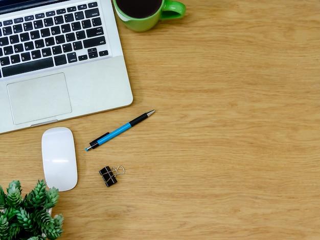 Widok z góry laptop, filiżanka kawy, kwiat i długopis na drewnianym stole. płaska świeża kopia spce. praca dla domu