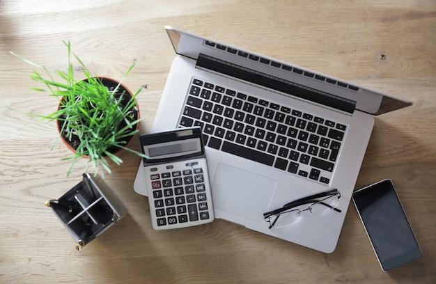 Widok z góry. laptop, kalkulator i smartfon na drewnianym stole