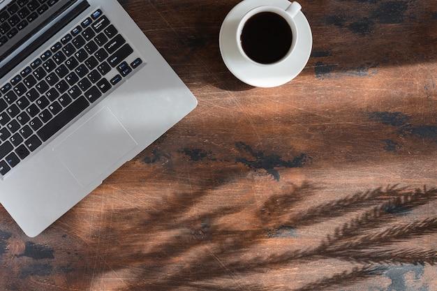 Widok z góry laptopa, boże narodzenie drewniane tła z gałęzi jodły, leżał płasko. zimowa kompozycja z laptopem i filiżanką kawy